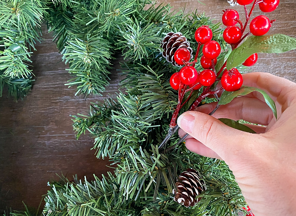 adding decorations to. a christmas wreath