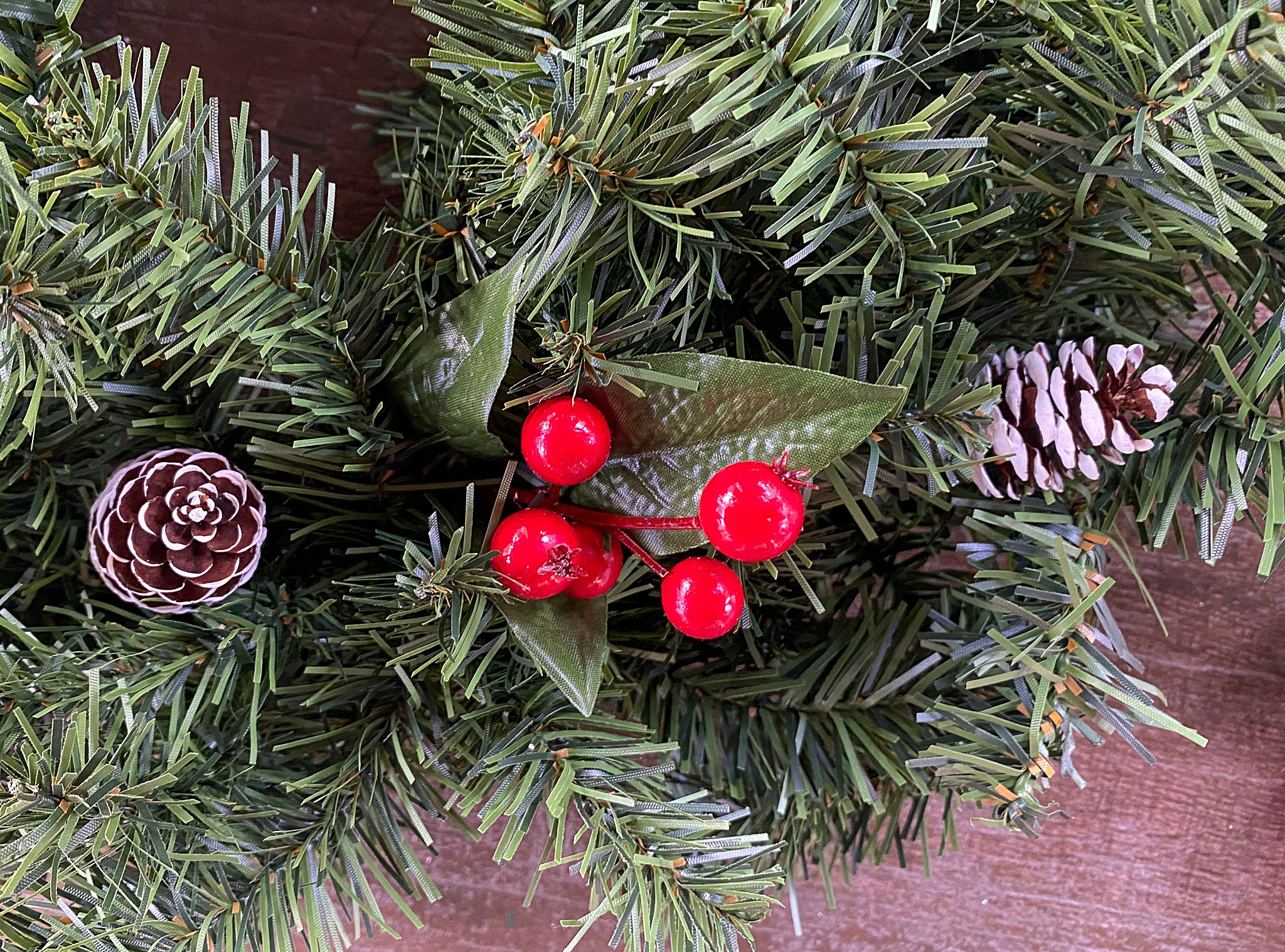 adding decorations to christmas. wreath